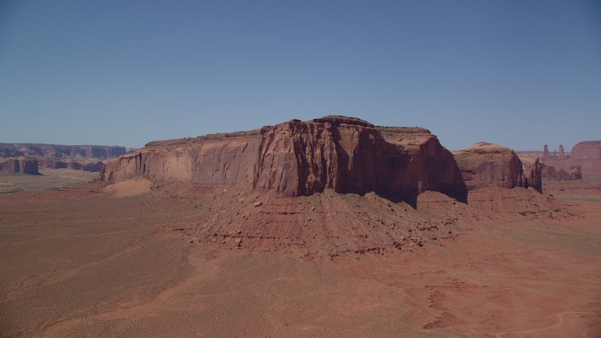 Flying by Spearhead Mesa, desert valley, Monument Valley, Utah, Arizona Aerial Stock Footage AX135_119