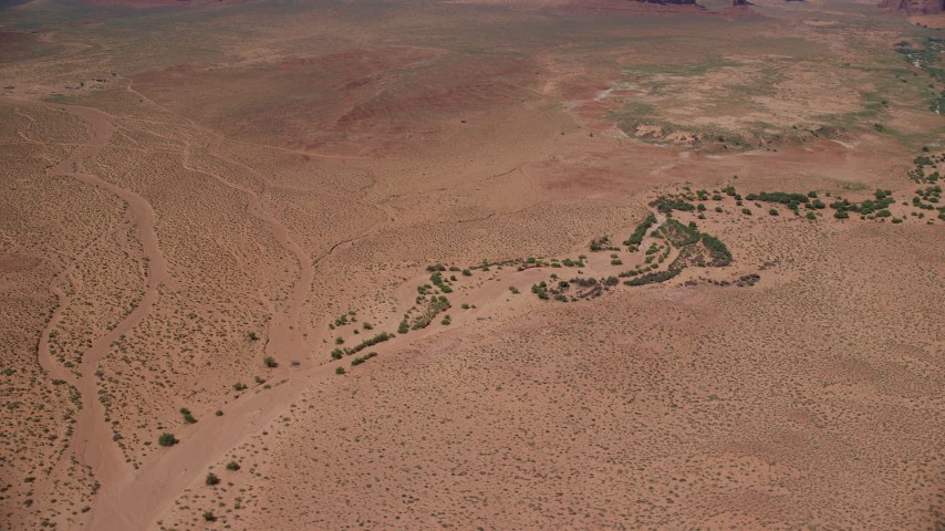 6K stock footage aerial video of orbiting part of a desert valley with vegetation, Monument Valley, Utah, Arizona Aerial Stock Footage | AX135_121