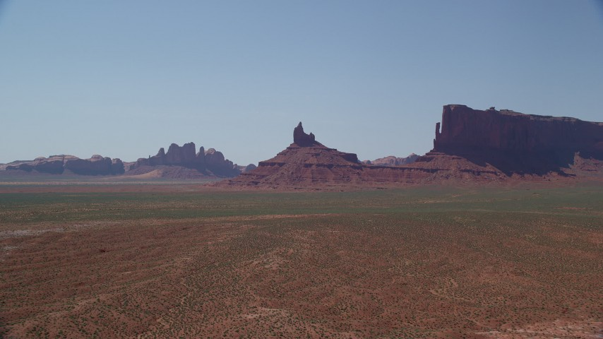 Approaching Rooster Rock, desert valley, Monument Valley, Utah, Arizona Aerial Stock Footage | AX135_123