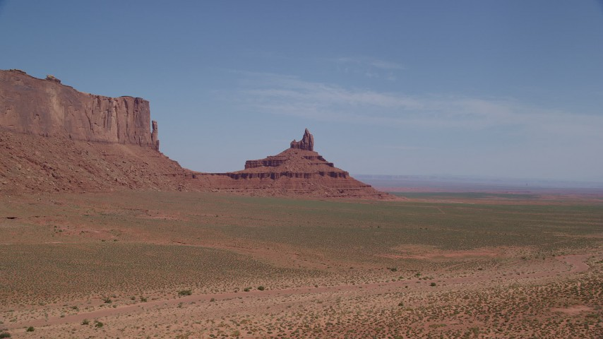 Descend and approach Rooster Rock, Monument Valley, Utah, Arizona Aerial Stock Footage | AX135_133