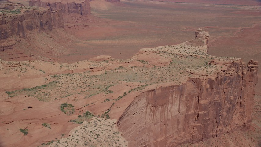 Flying over Meridian Butte, pan right to desert, Monument Valley, Utah, Arizona Aerial Stock Footage | AX135_154
