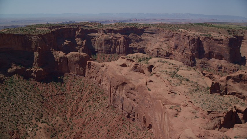 6K stock footage aerial video of flying past Hunt's Mesa and sparse desert vegetation, Monument Valley, Utah, Arizona Aerial Stock Footage | AX135_165
