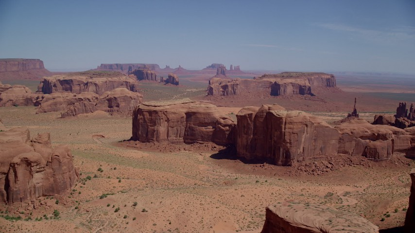 Flying by desert buttes and mesas, Monument Valley, Utah, Arizona Aerial Stock Footage | AX135_176