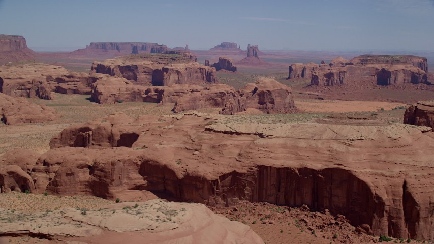 Flying by desert buttes and mesas, Monument Valley, Utah, Arizona Aerial Stock Footage | AX135_178