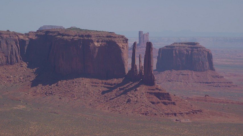 Flying by mesas and buttes in a hazy desert valley, Monument Valley, Utah, Arizona Aerial Stock Footage | AX135_184