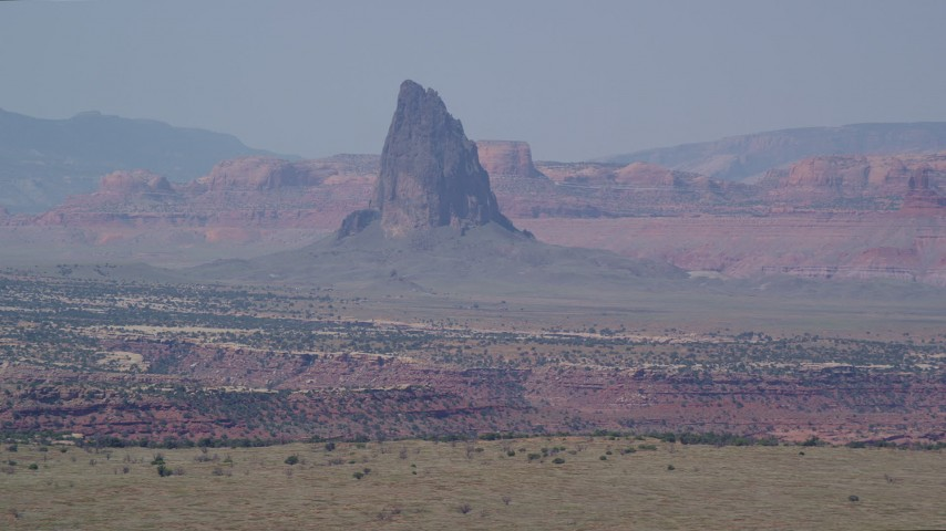Flying by tall butte, hazy desert valley, Monument Valley, Utah, Arizona Aerial Stock Footage | AX135_185
