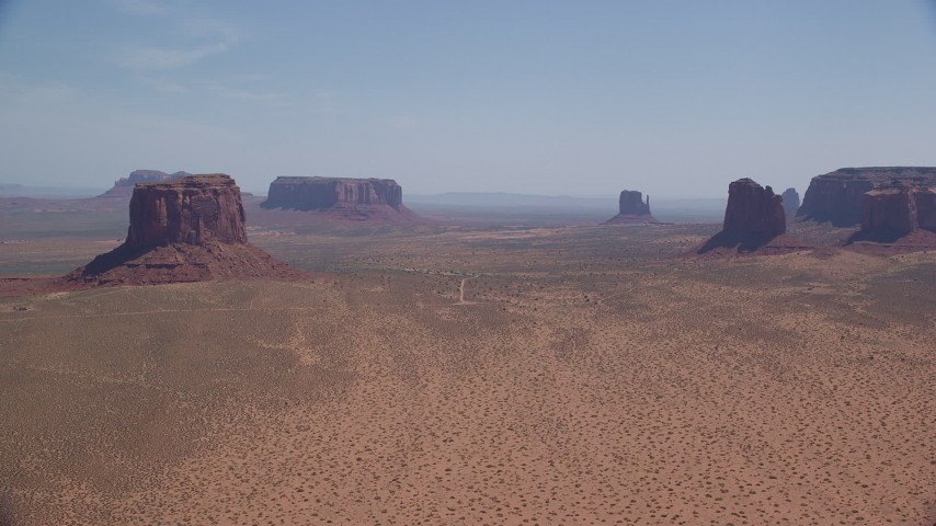 6K stock footage aerial video of passing by open desert with buttes and mesas, Monument Valley, Arizona, Utah Aerial Stock Footage | AX135_193