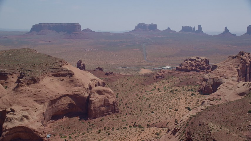 Flying by Monument Valley Buttes, Navajo Nation Reservation, Utah, Arizona Aerial Stock Footage | AX135_199