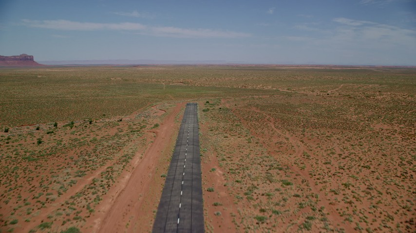 6K stock footage aerial video of flying over a runway toward wide desert valley, Monument Valley Airport, Utah Aerial Stock Footage | AX136_001