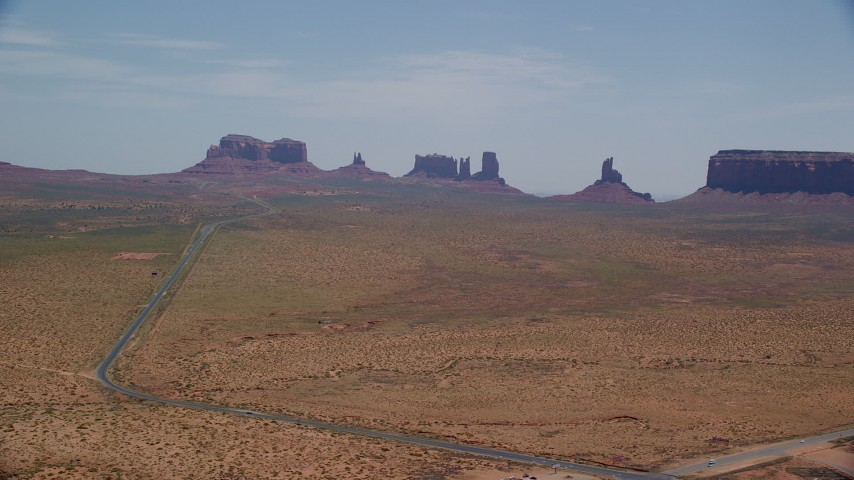 6K stock footage aerial video of flying by Highway 163 leading to buttes in Monument Valley Arizona, Utah Aerial Stock Footage | AX136_002
