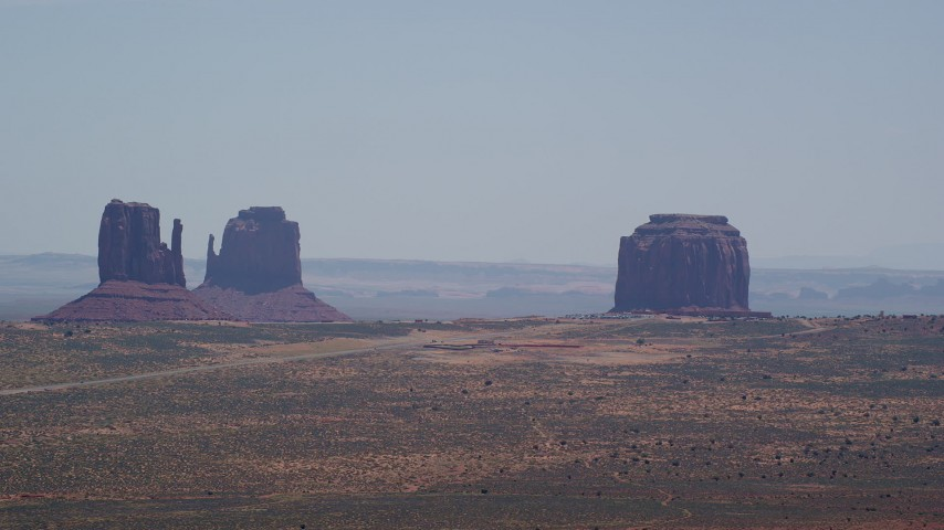 Flying by buttes, hazy desert valley, Monument Valley, Utah, Arizona Aerial Stock Footage | AX136_004
