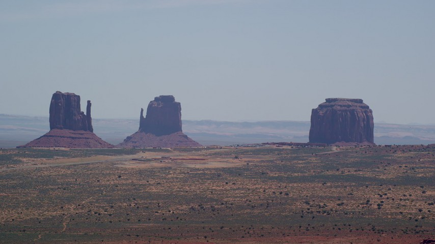 Flying by buttes, hazy desert valley, Monument Valley, Utah, Arizona Aerial Stock Footage | AX136_005