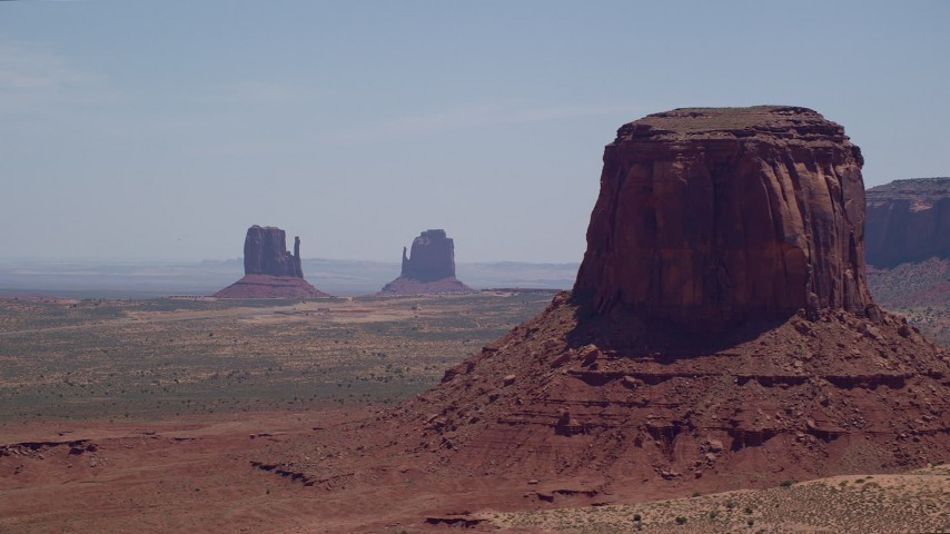 Flying by buttes, hazy desert valley, Monument Valley, Utah, Arizona Aerial Stock Footage | AX136_006