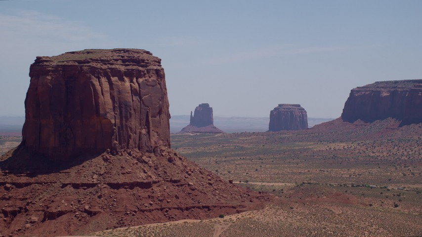 Flying by desert buttes in a hazy valley, Monument Valley, Utah, Arizona Aerial Stock Footage | AX136_007
