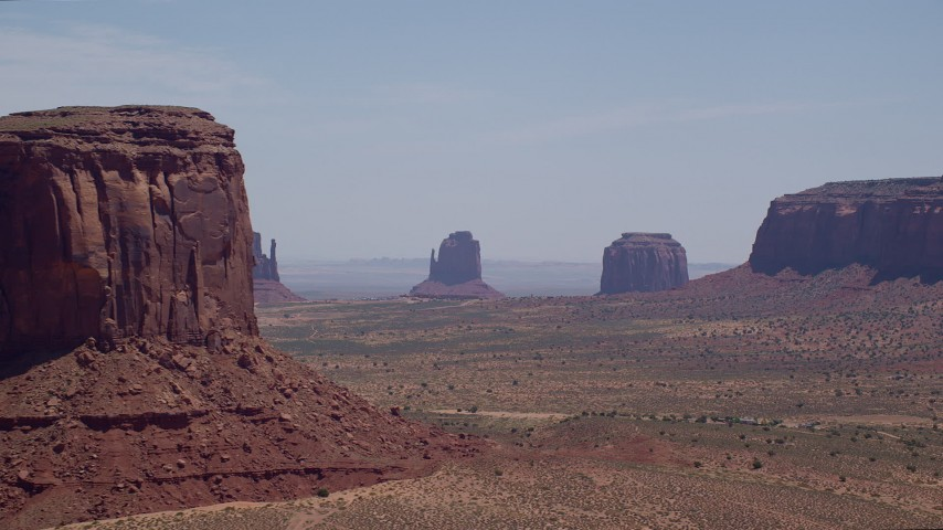Flying by desert buttes, hazy valley, Monument Valley, Utah, Arizona Aerial Stock Footage | AX136_008