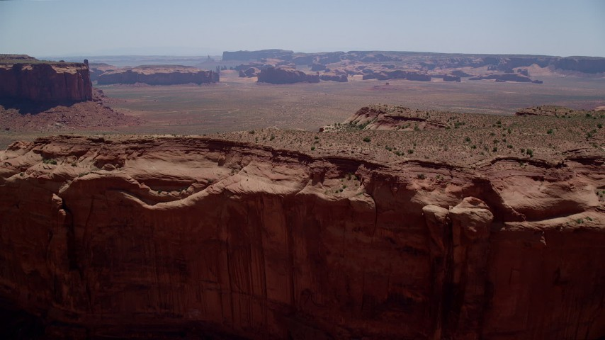 Flying over Mitchell Mesa, approaching buttes, Monument Valley, Utah, Arizona Aerial Stock Footage | AX136_012