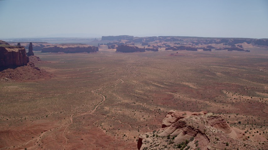 6K stock footage aerial video of approaching buttes and mesas from Mitchell Mesa, Monument Valley, Utah, Arizona Aerial Stock Footage | AX136_013