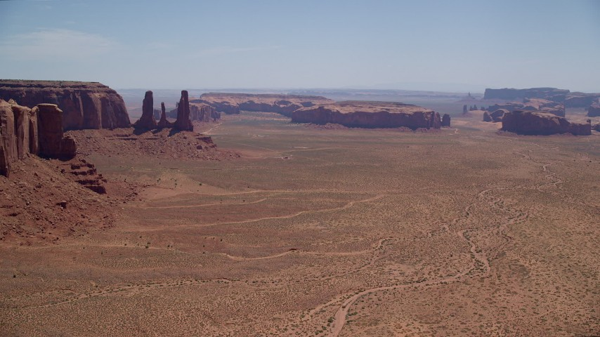 Fly by Three Sisters, Rain God Mesa, Thunderbird Mesa, Monument Valley, Utah, Arizona Aerial Stock Footage | AX136_014