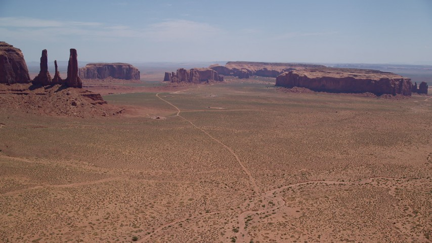 6K stock footage aerial video wide view of several mesas and buttes in a desert valley, Monument Valley, Utah, Arizona Aerial Stock Footage | AX136_016