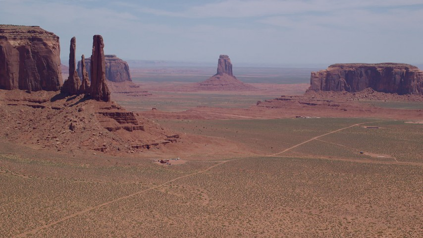 Flying by buttes, desert valley, Monument Valley, Utah, Arizona Aerial Stock Footage | AX136_017