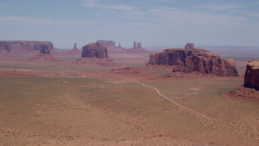 Flying by buttes, hazy desert valley, Monument Valley, Utah, Arizona Aerial Stock Footage | AX136_019