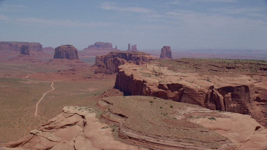 6K stock footage aerial video of slowly passing buttes and a mesa in a desert valley, Monument Valley, Utah, Arizona Aerial Stock Footage | AX136_020