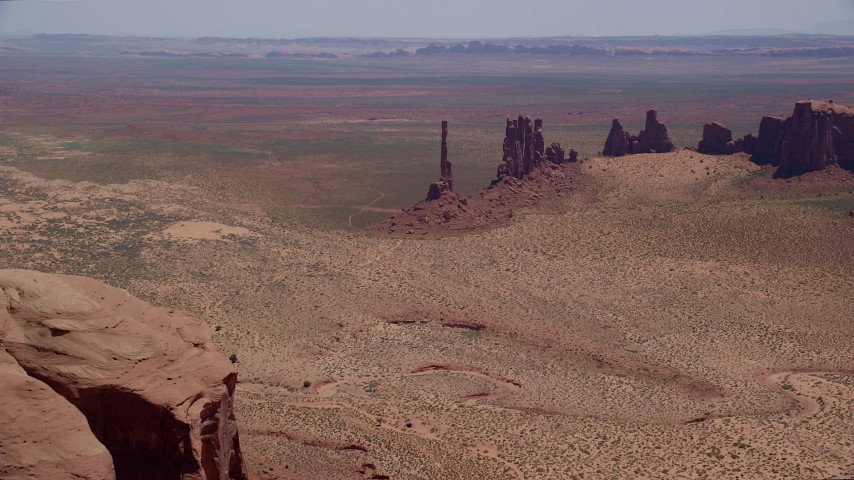 Approaching Totem Pole Butte, Yei Bi Chei Butte, Monument Valley, Utah, Arizona Aerial Stock Footage | AX136_021