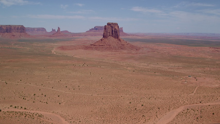 Tilt up from desert to reveal East Mitten Butte, Monument Valley, Utah, Arizona Aerial Stock Footage AX136_027