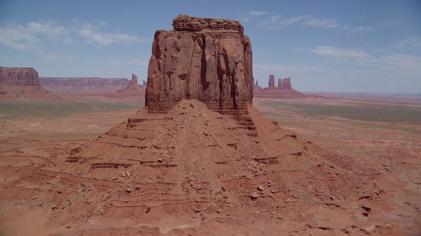 6K stock footage aerial video tilt from desert valley to reveal East Mitten Butte, Monument Valley, Utah, Arizona Aerial Stock Footage | AX136_030