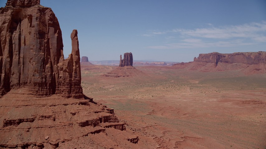 Flying by desert buttes and mesas, Monument Valley, Utah, Arizona Aerial Stock Footage | AX136_032