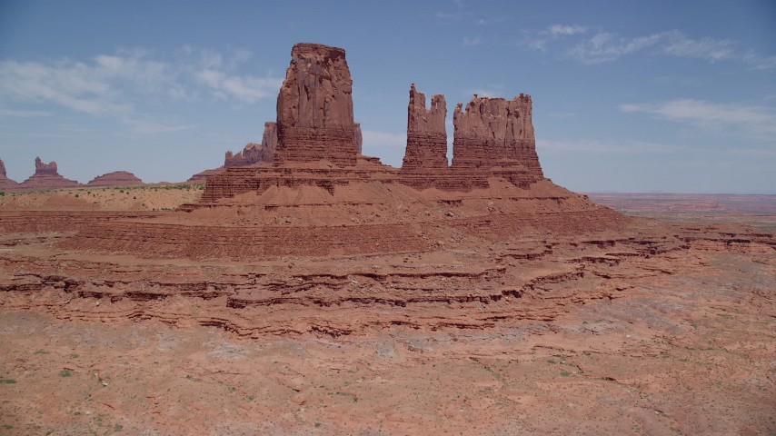 Flying over desert, tilt up to reveal buttes, Monument Valley, Utah, Arizona Aerial Stock Footage | AX136_036