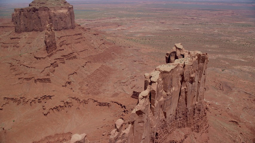 6K stock footage aerial video of flying over Stagecoach Butte toward a desert valley, Monument Valley, Utah, Arizona Aerial Stock Footage | AX136_039