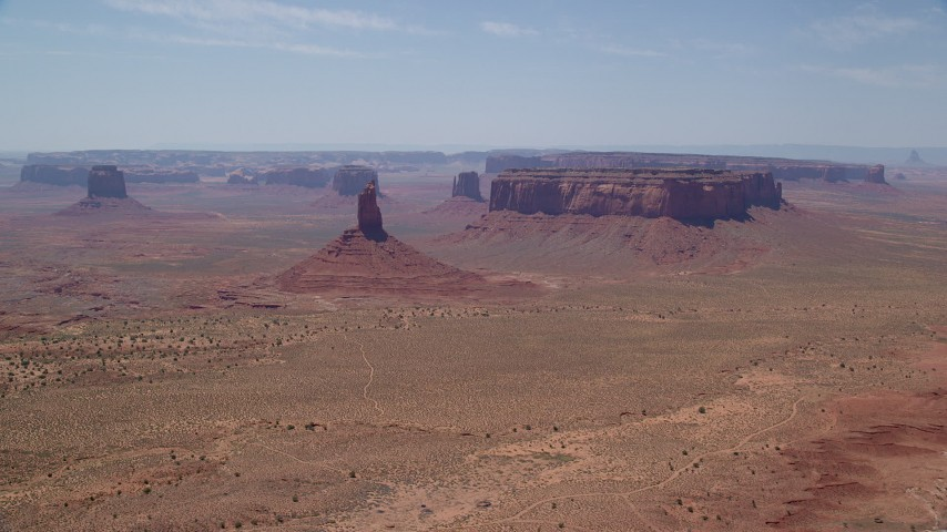Flying away from Big Indian Butte, Sentinel Mesa, Monument Valley, Utah, Arizona Aerial Stock Footage | AX136_042
