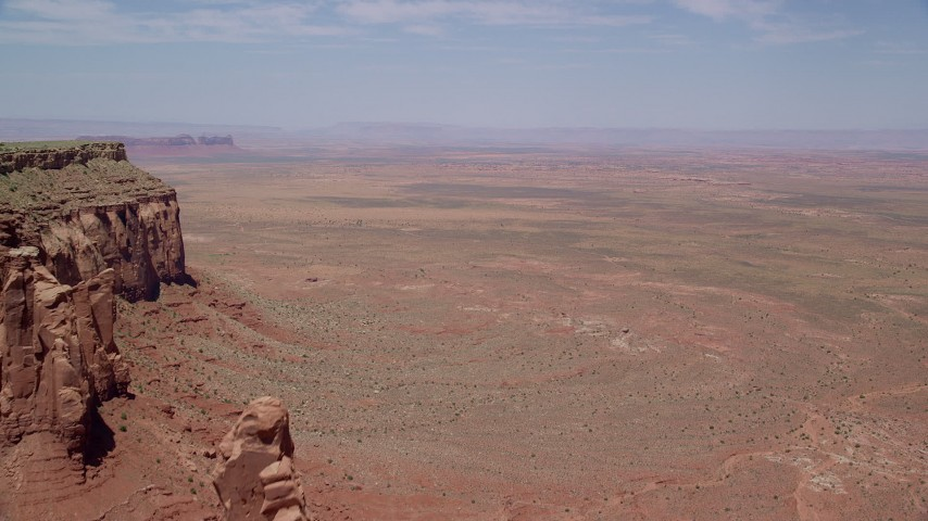 6K stock footage aerial video of a wide view of open hazy desert valley north of Monument Valley, Utah, Arizona Aerial Stock Footage | AX136_044