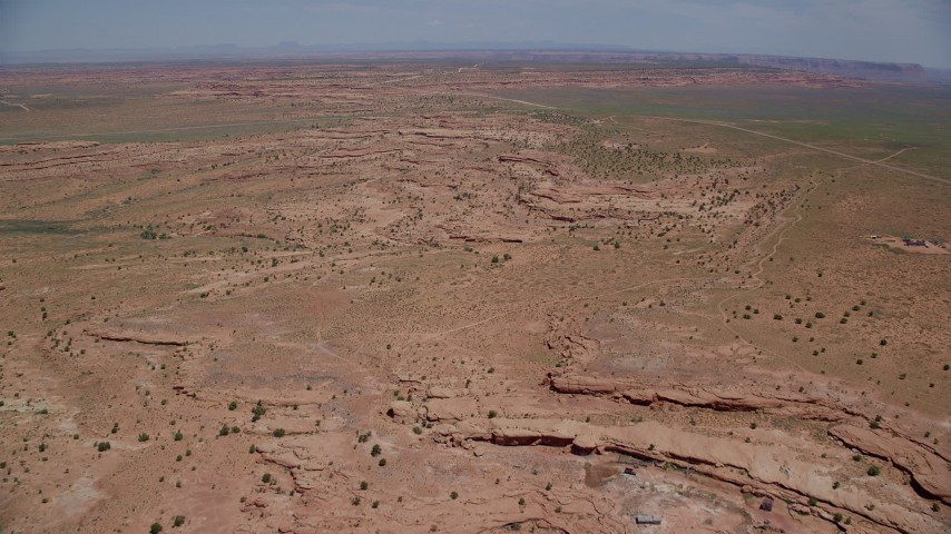 Flying over open desert just north of Monument Valley, Utah, Arizona Aerial Stock Footage | AX136_046