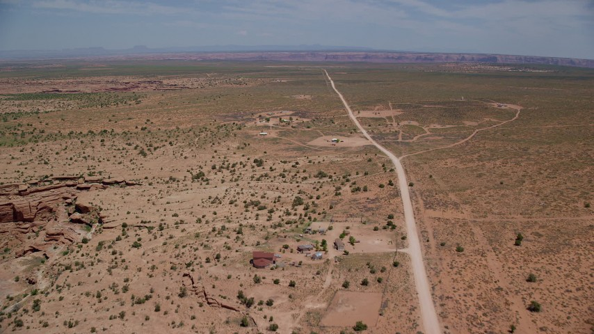 Flying over rural homes near Douglas Mesa Road, Navajo Nation Reservation, Utah, Arizona Aerial Stock Footage | AX136_051