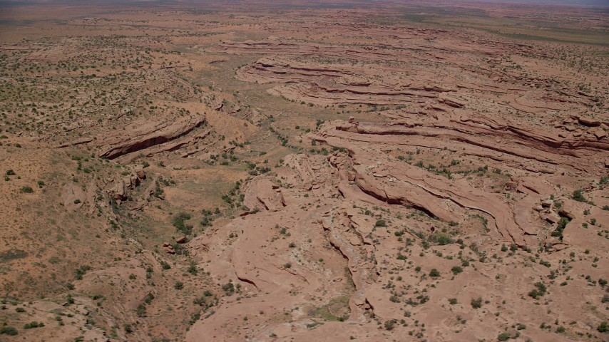 Flying by desert rock formations, Navajo Nation Reservation, Utah, Arizona Aerial Stock Footage | AX136_053