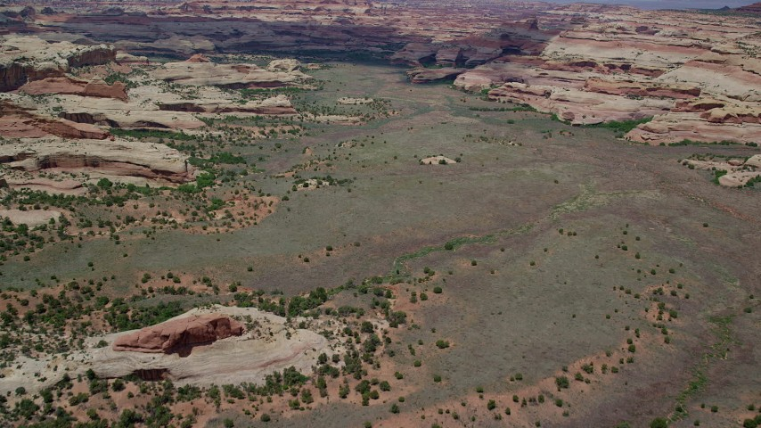 6K stock footage aerial video of flying over valley surrounded by rock formations in Canyonlands National Park, Utah Aerial Stock Footage | AX136_203