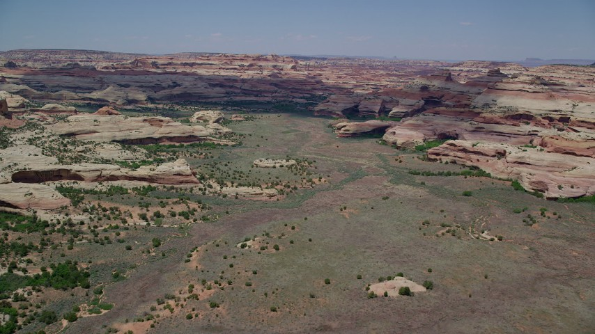 6K stock footage aerial video of flying over valley surrounded by rock formations, Canyonlands National Park, Utah Aerial Stock Footage | AX136_204