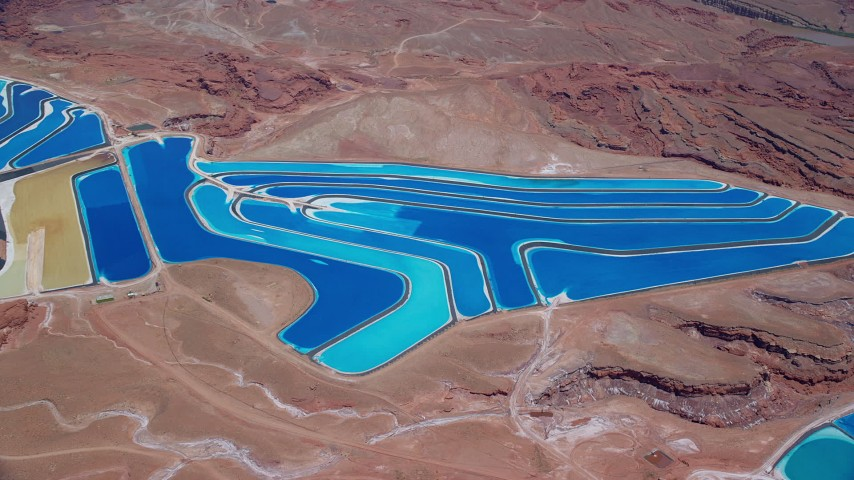 6K stock footage aerial video of potash ponds in desert valley, tilt while approaching, Moab, Utah Aerial Stock Footage | AX136_271