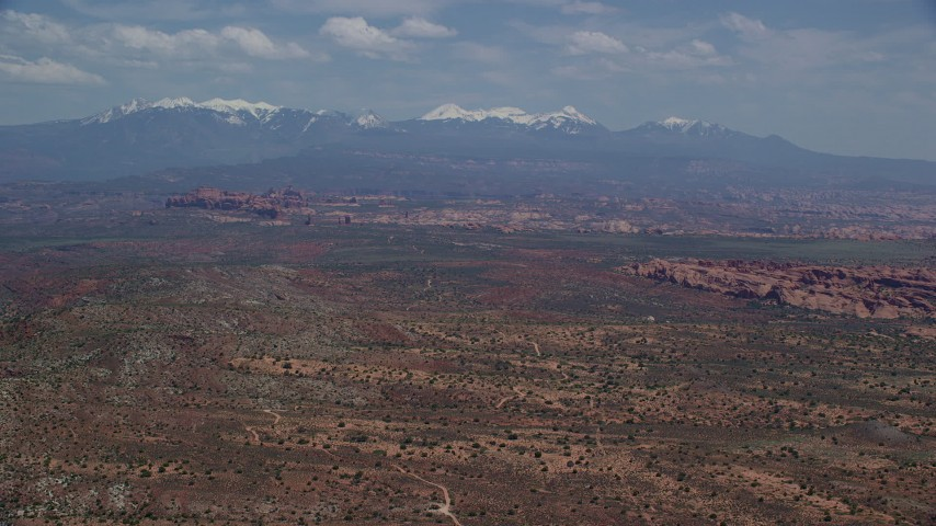 6K stock footage aerial video of desert rock formations, distant snow-capped mountains, Arches National Park, Utah Aerial Stock Footage   AX137_006