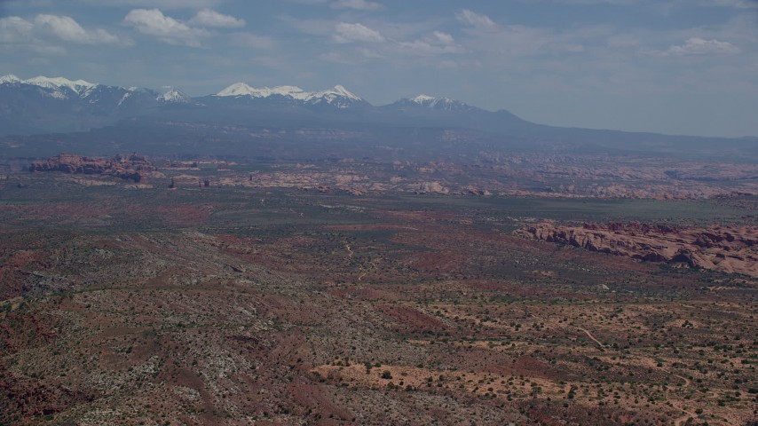 Flying by rock formations, snow-capped mountains, Arches National Park, Utah Aerial Stock Footage | AX137_007