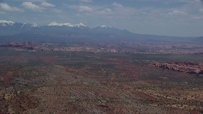 6K stock footage aerial video of a wide view of rock formations, snow-capped mountains, Arches National Park, Utah Aerial Stock Footage | AX137_008