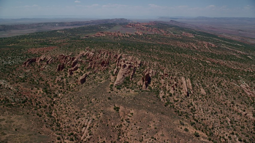 Fly over rock fins and vegetation, Devil's Garden, Arches National Park, Utah Aerial Stock Footage | AX137_018