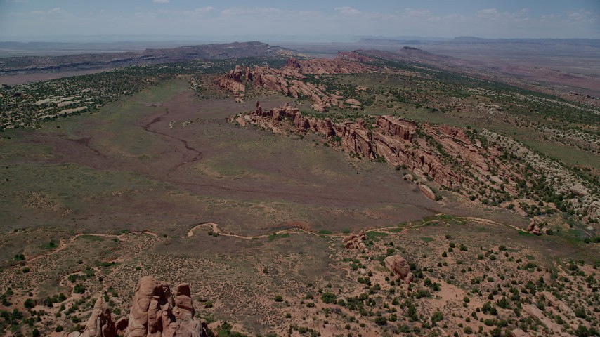 6K stock footage aerial video of approaching dry river bed and Eagle Park, Arches National Park, Utah Aerial Stock Footage | AX137_022