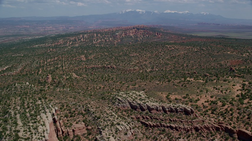 Fly over cliffs and desert vegetation, Devil's Garden, Arches National Park, Utah Aerial Stock Footage | AX137_043
