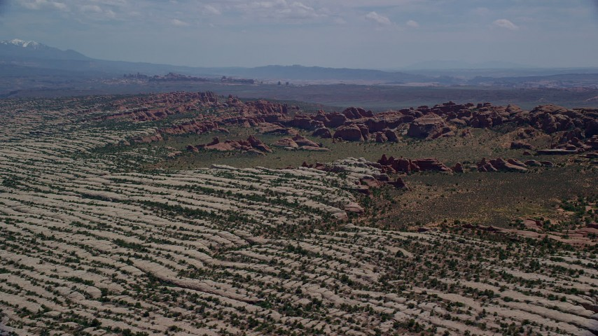 6K stock footage aerial video of passing rock formations and desert plants in Devil's Garden, Arches National Park, Utah Aerial Stock Footage | AX137_052