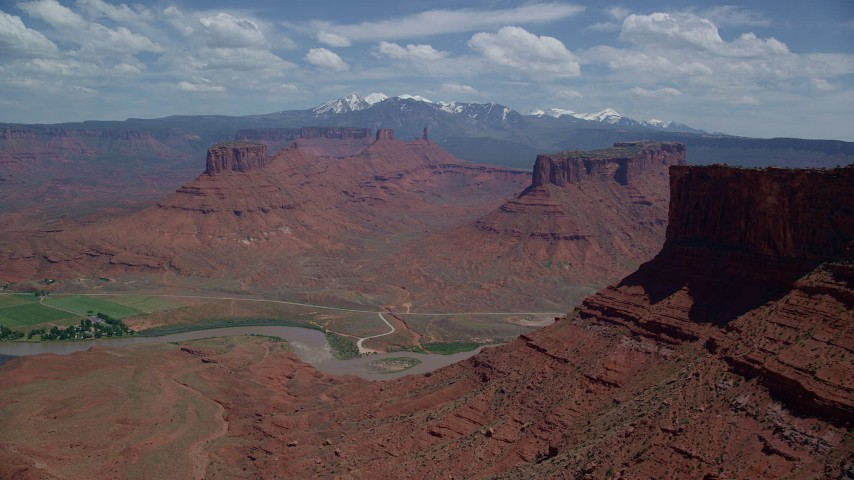 Mesas and Buttes seen from Colorado River and Parriott Mesa, Moab, Utah Aerial Stock Footage | AX137_086