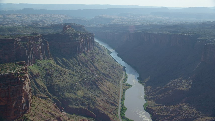 Fly over Colorado River toward cliffs, Big Bend, Arches National Park, Utah Aerial Stock Footage | AX138_028