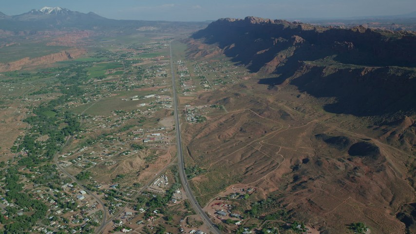 Highway cutting through a small desert town, Moab, Utah Aerial Stock Footage | AX138_041